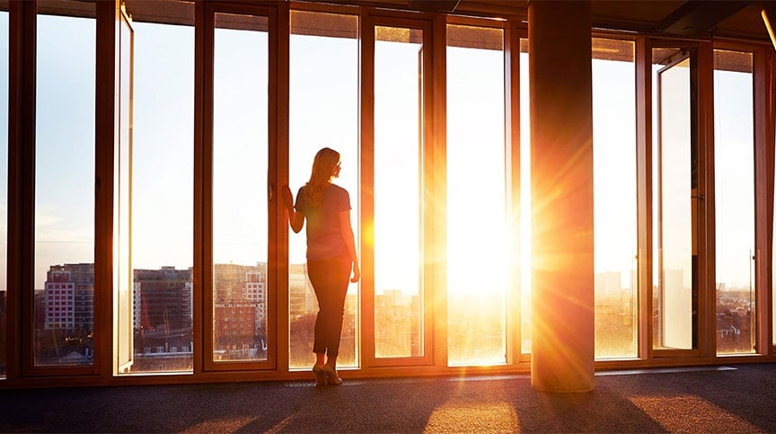 image of business woman looking out window rethinking leadership