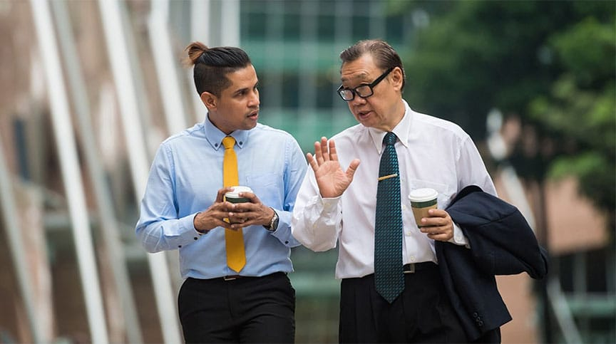 senior business man walking with junior business man implementing mentoring at work