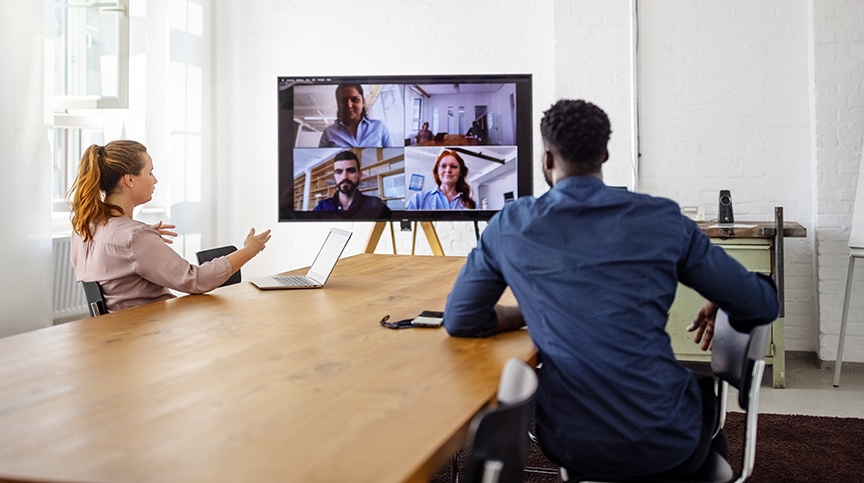 image of 2 colleagues in meeting room on virtual call with other team members representing hybrid workforce